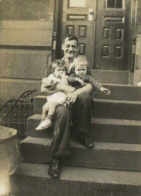 Man holding two small children on steps, Philadelphia.