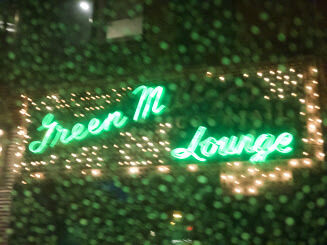 The sign for the Green Mill, a historic jazz lounge, on a rainy day.