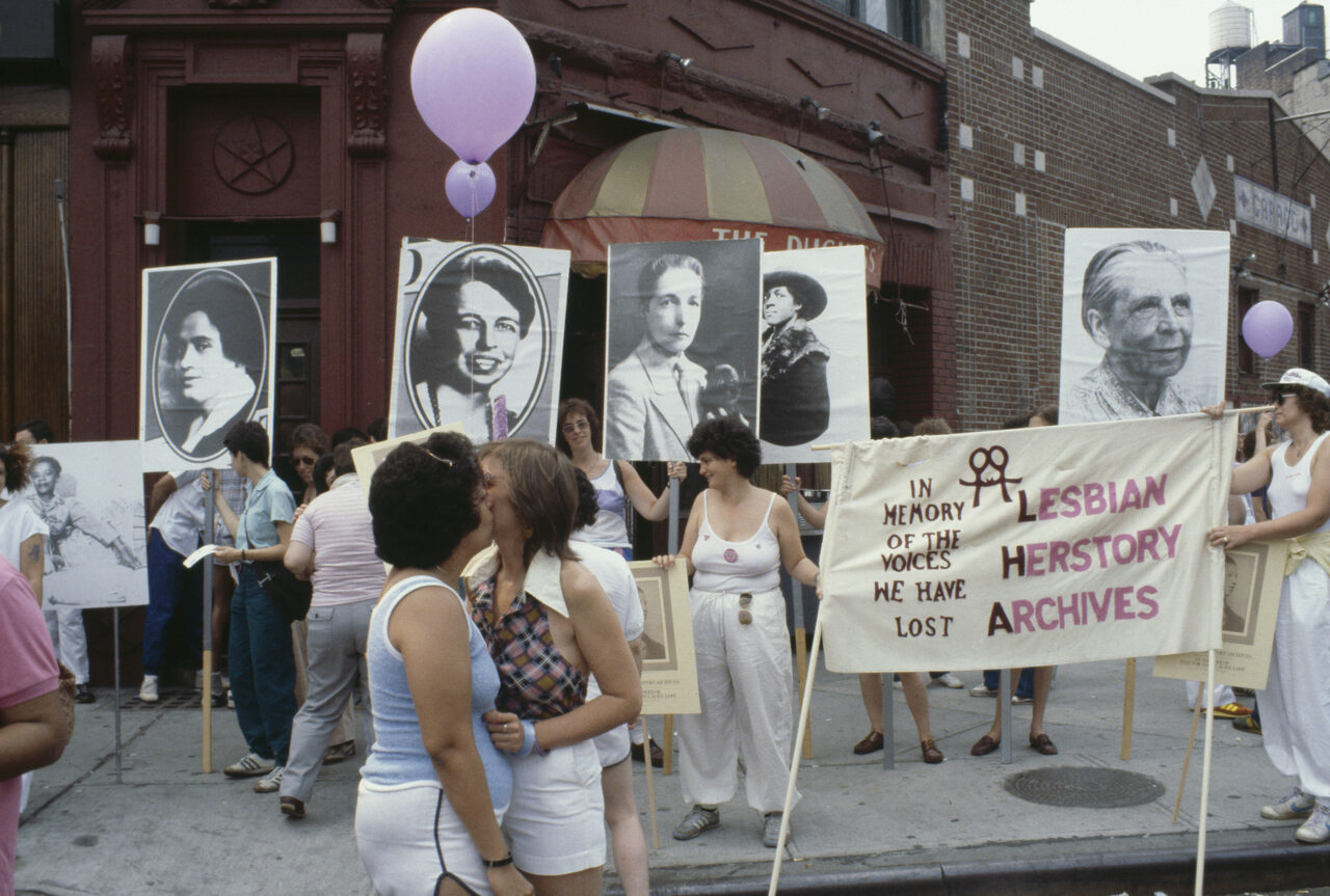 Women kiss, celebrate, and hold up a banner for the Lesbian Herstory Archives in front of the Duchess Bar, then a popular lesbian bar in Greenwich Village, at Pride in 1982.