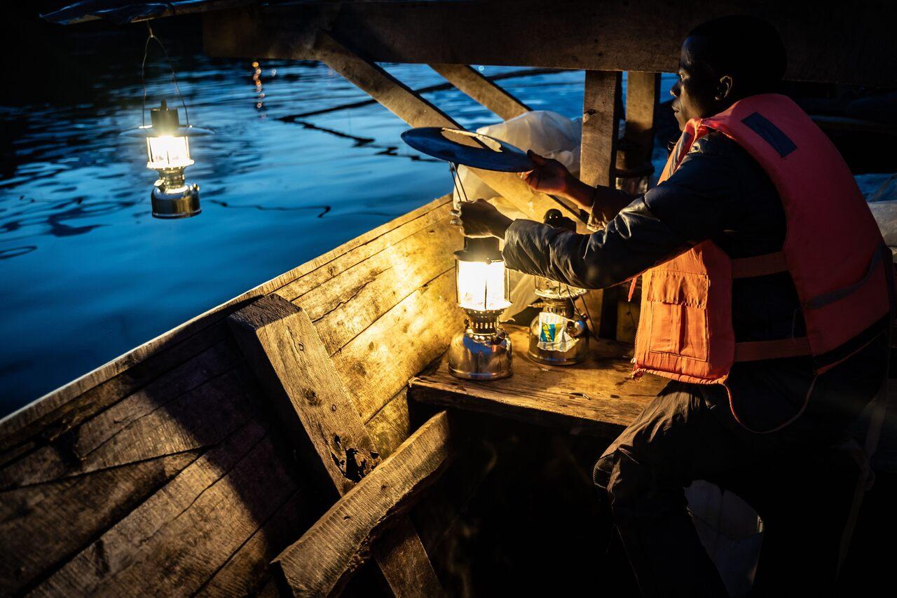 A fisherman lights lanterns on Lake Kivu in 2019.