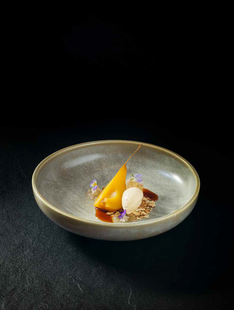 """This dessert from <em>Hiakai</em> features pears poached in <em>manono</em> tree bark with <em>horopito</em> (pepper tree) ice cream and almond """"soil"""" made of toasted almonds and crushed biscuits."""