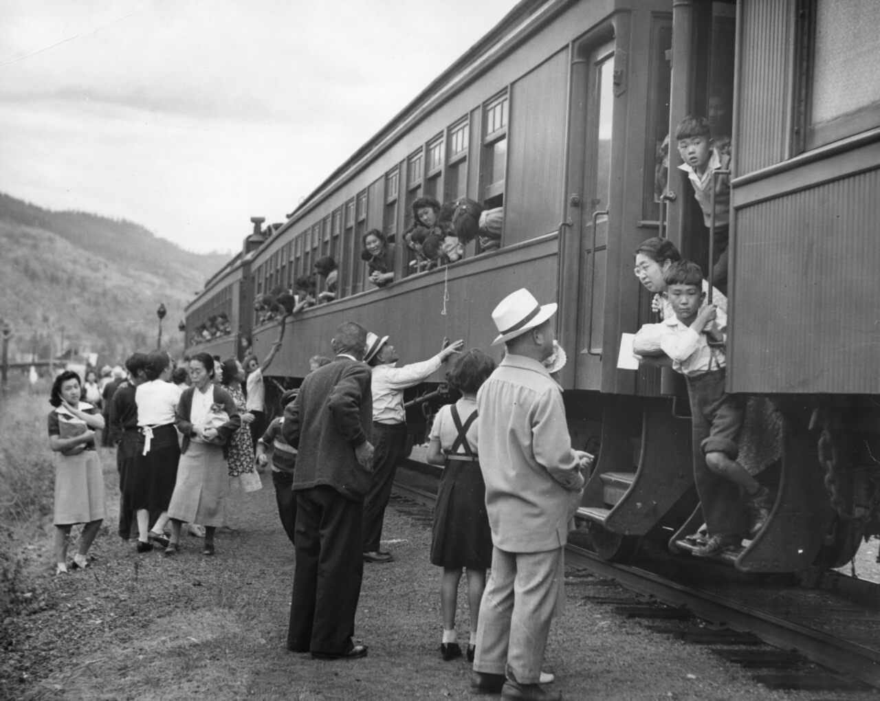 "Displaced Japanese Canadians leaving the Vancouver area (possibly Slocan Valley) after being prohibited by law from entering a ""protected area"" within 100 miles of the coast. The woman on the left in this Leonard Frank photograph holding the book is Nobuko Morimoto, the woman in dark cardigan is Tei Terashita, and the young woman leaning out of train is identified as Kazuyo Kawabata."