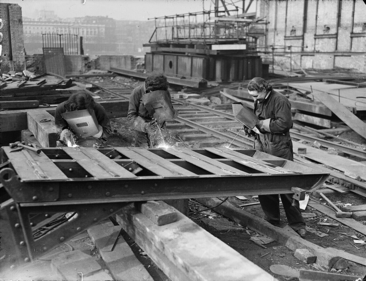"""A photo from The Daily Herald, with the original caption """"Girl acetylene welders were at their job as usual today, cutting the girders of the temporary Waterloo Bridge, which is being dismantled."""""""