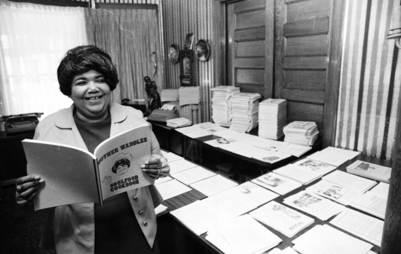 """Waddles, with copies of her poetry-infused """"Soul Food Cookbook."""""""
