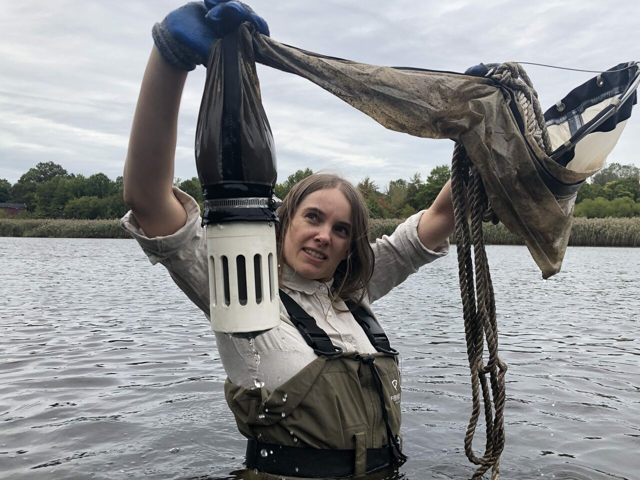 Sally Warring holds up her plankton net, teeming with microbes.
