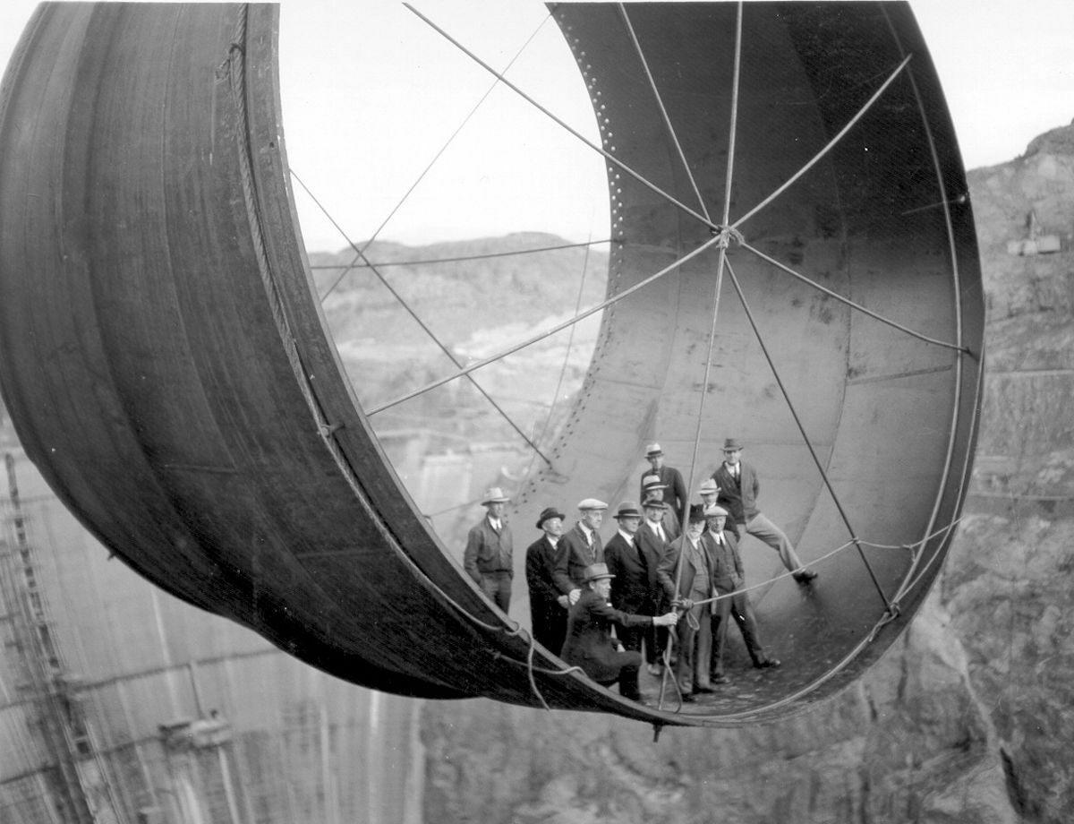 Members of the Boulder City Consulting Board and other officials standing in a section of pipe over the Hoover Dam, 1935.