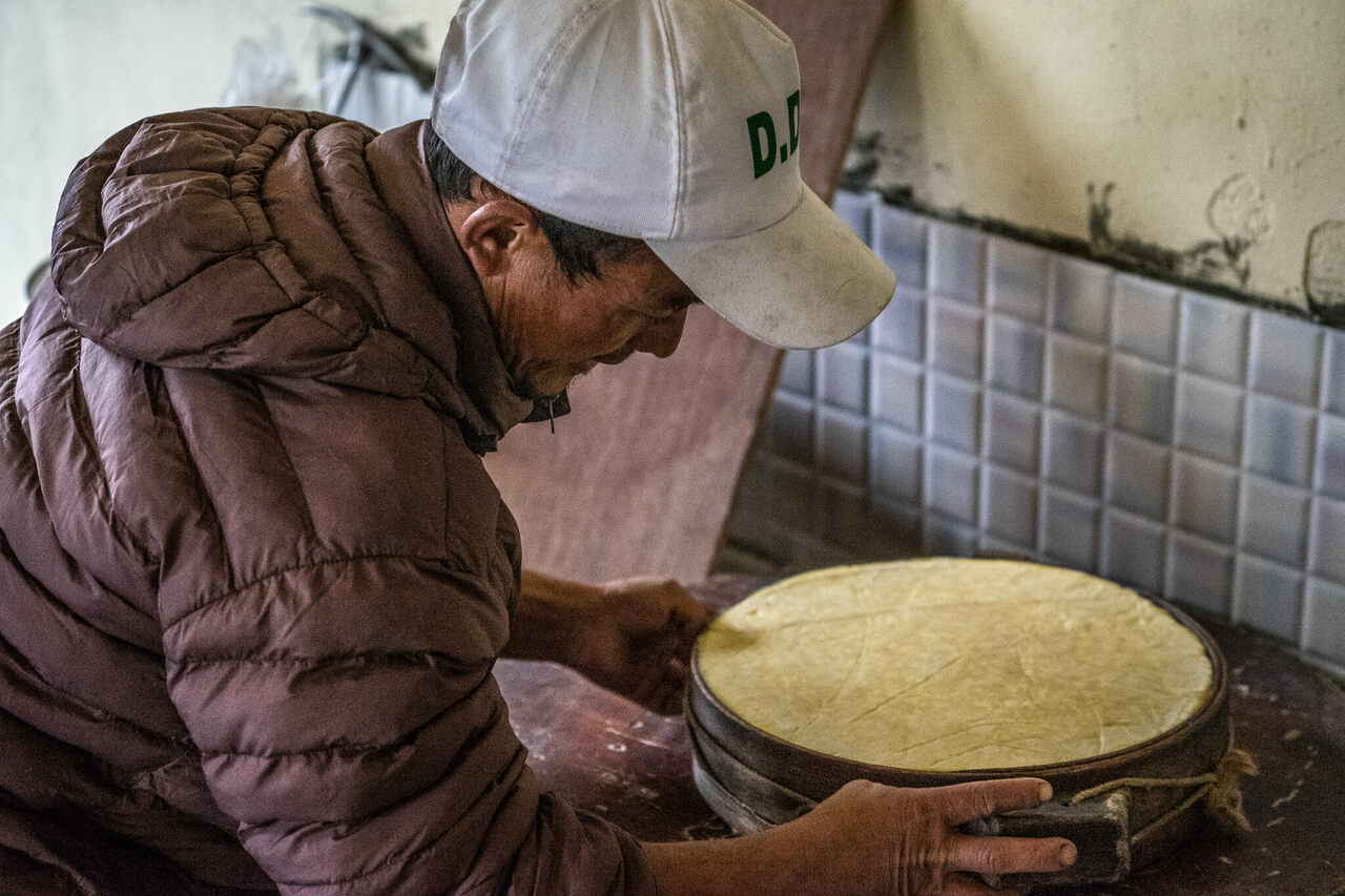 Nima Tamang molds a hefty wheel of yak cheese.