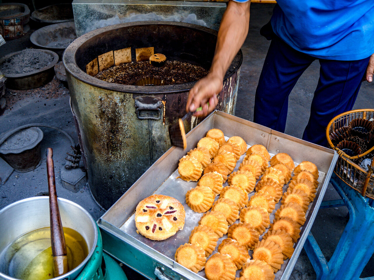 A baker at Kanoom Farung Lan Mea Pao picks freshly baked cakes out of the charcoal brazier and moves them to a metal box to cool.