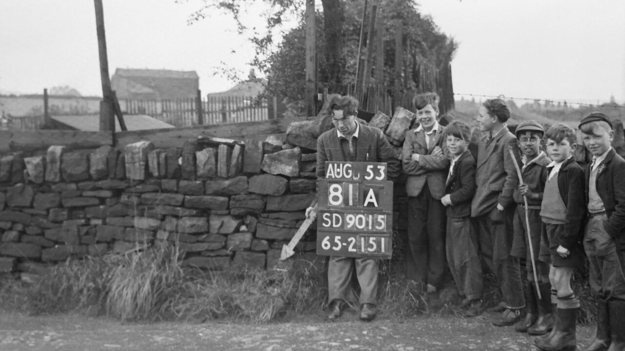 An Ordnance Survey worker points his arrow at a revision point, while laughing children look on.
