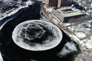 The huge ice disk dwarfs a nearby parking garage.