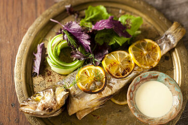 A saffron and rose water dressing lends unexpected perfume to a roasted sea bass stuffed with walnuts.