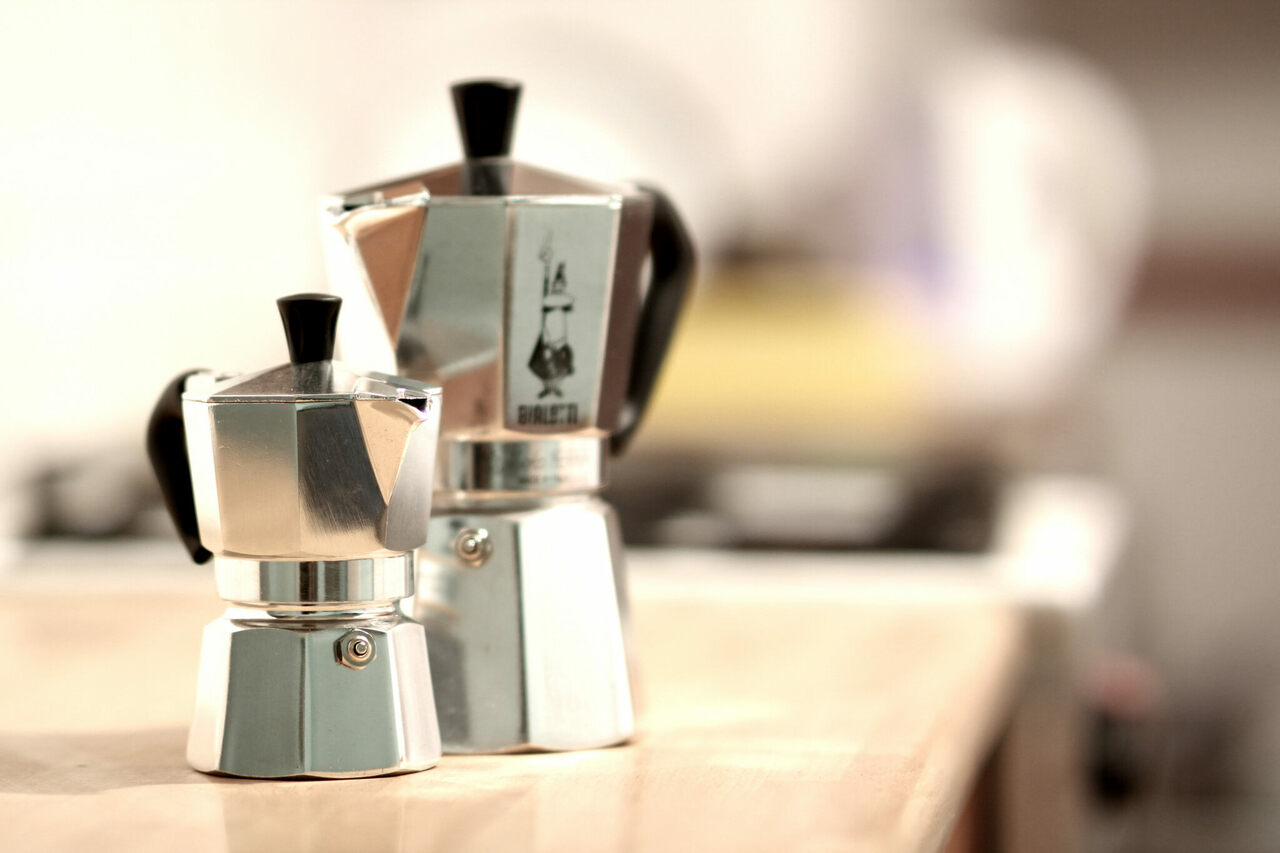 Two Moka pots, together on a counter.