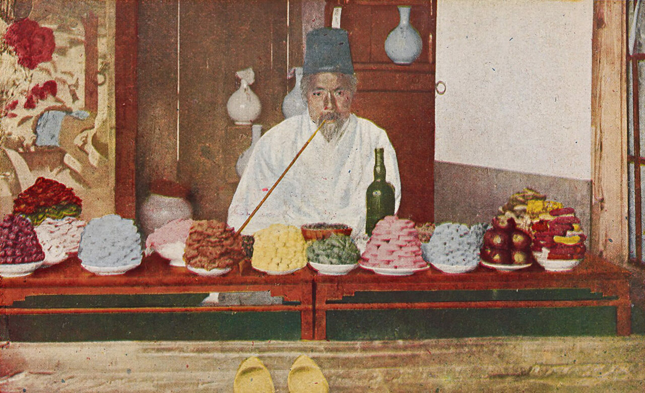 A shopkeeper in Seoul selling piles of festival treats, in the early 20th.