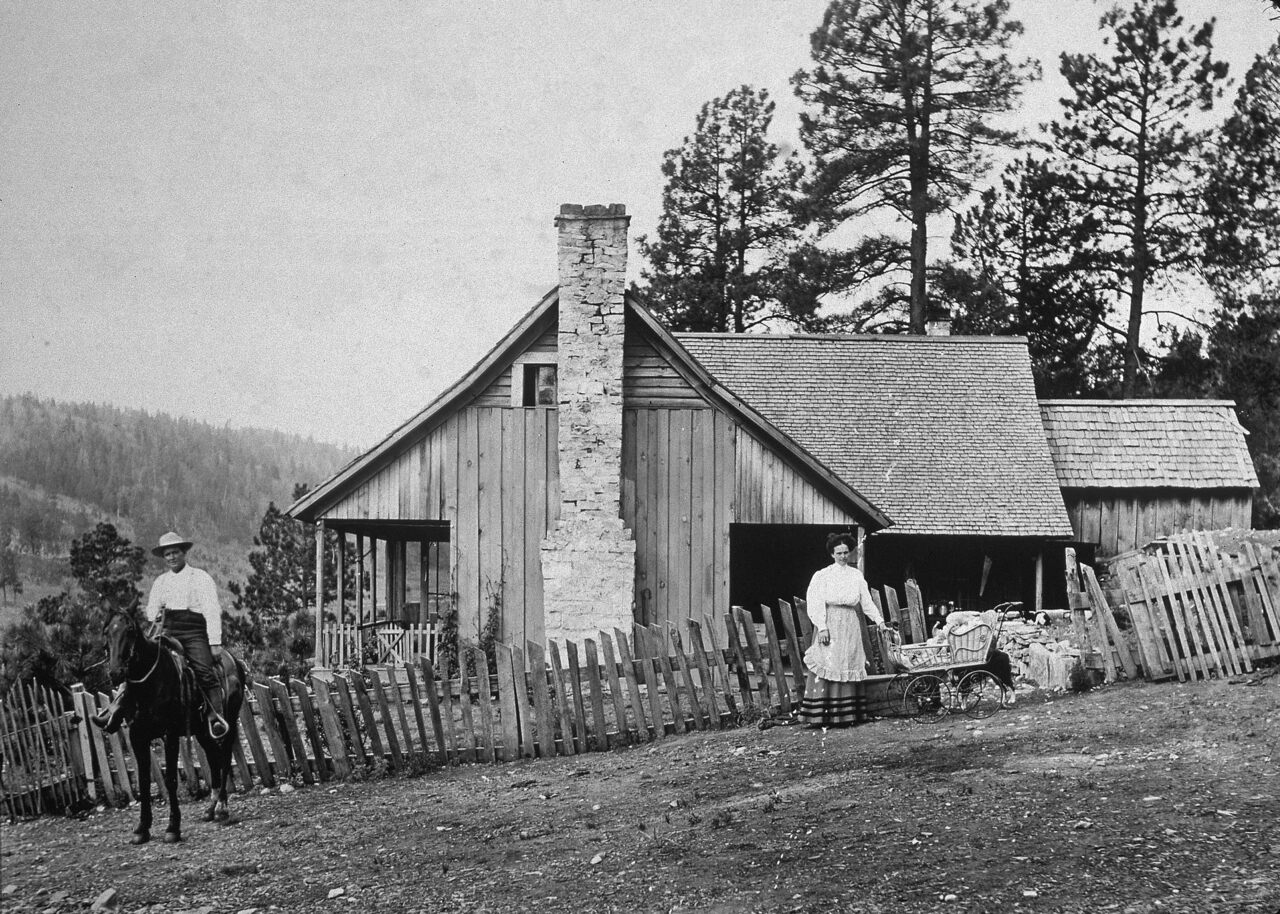 A family poses outside their homestead, somewhere out west, in the late 19th century.