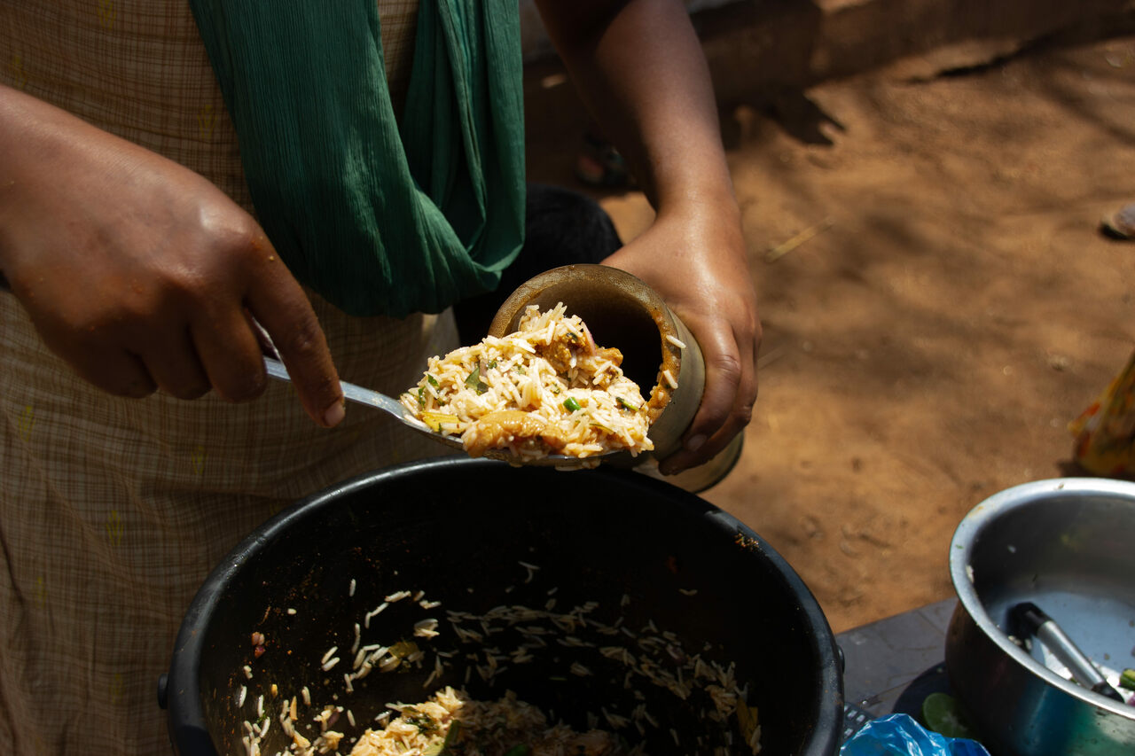 At her roadside stand, Sowbhagya Lakshmi fills a green bamboo shoot with a mixture of rice, chicken, and spices.