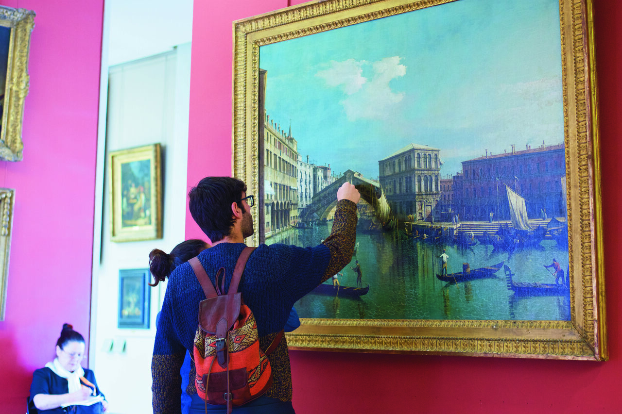 "A visitor to the Louvre is tempted by Canaletto's 18th-century painting ""The Rialto Bridge in Venice."""