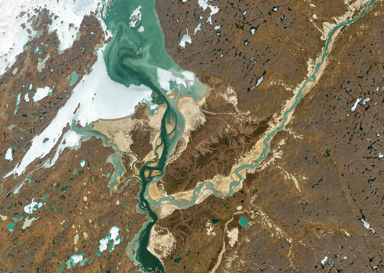 Amid ice and tundra, the lighter Hayes River flows from the northeast (top right) into the dark Back River in Nunavut, Canada, but remains distinct from it for 10 miles.