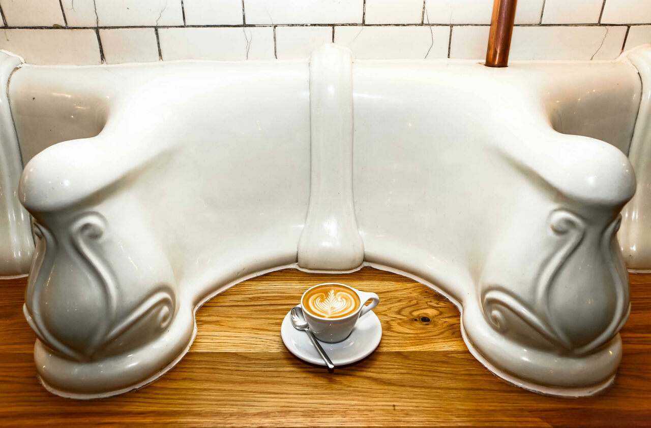 Attendant proudly serves coffee and snacks atop refurbished urinals.