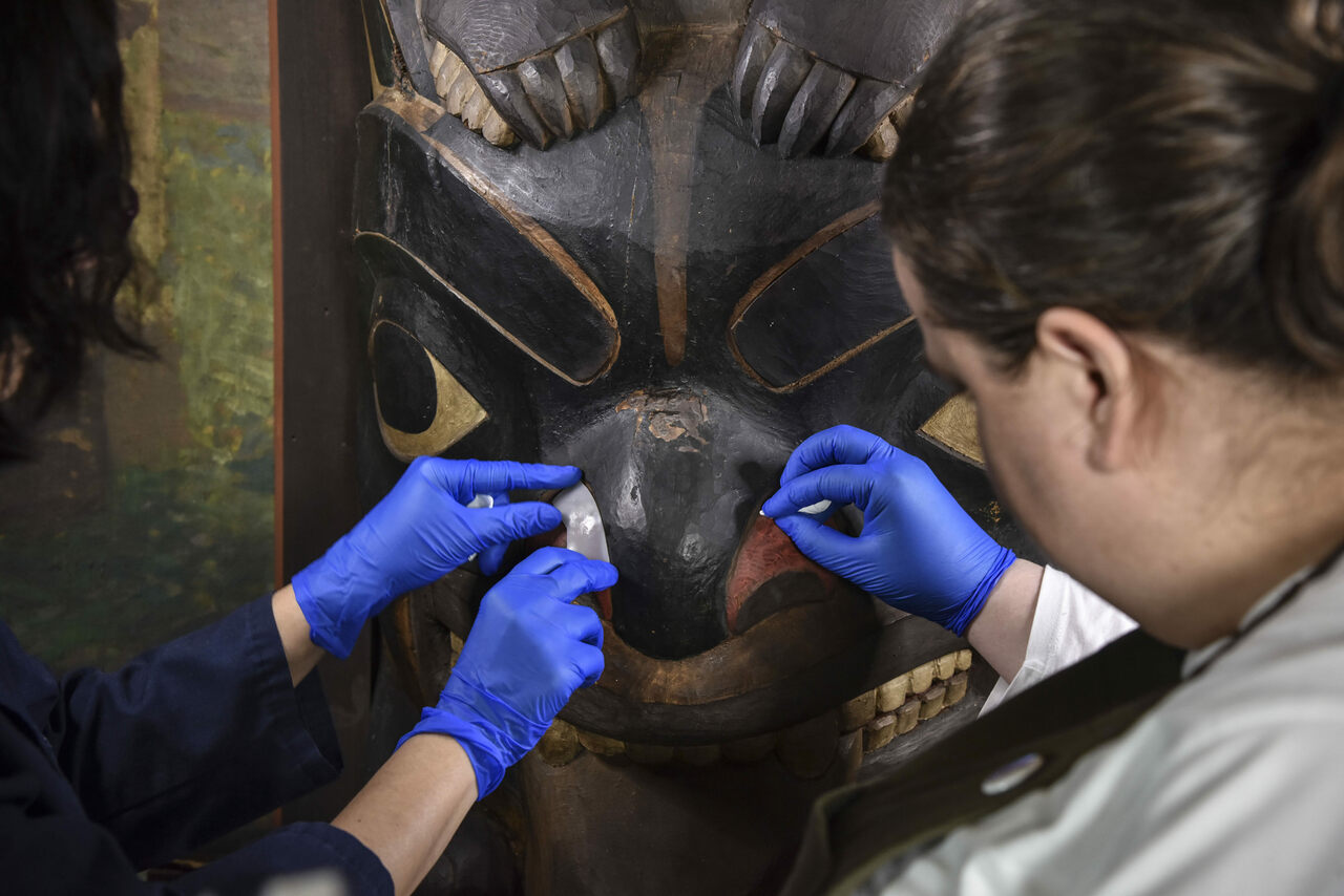 Soraya Alcala Carbonero (left) and Madeleine Neiman (right), assistant conservators, treat a Tsimshian house post.