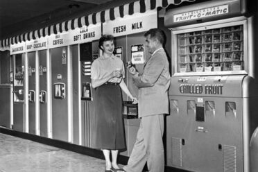 Two people chat by a chilled fruit machine, among other vending machines, in 1959.