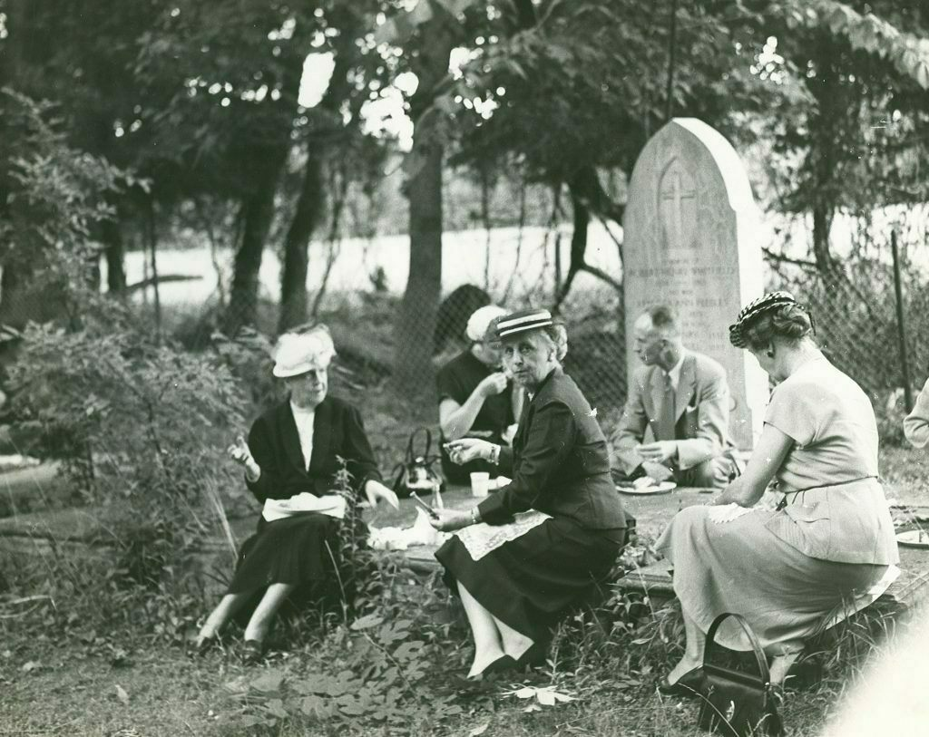 A small group picnics on ledger-style tombstones in Historic St. Luke's Ancient Cemetery. The photo is not dated but is believed to have been taken prior to St. Luke's 1957 Pilgrimage Service.