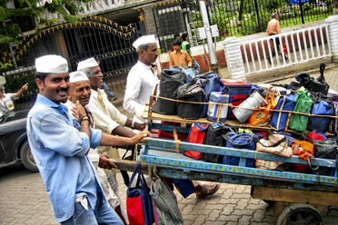 Four <em>dabbawalas</em> haul lunches, packed in <em>dabbas</em>, through the streets of Mumbai.