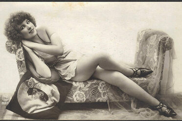 A flapper posing with a flapper pillow.