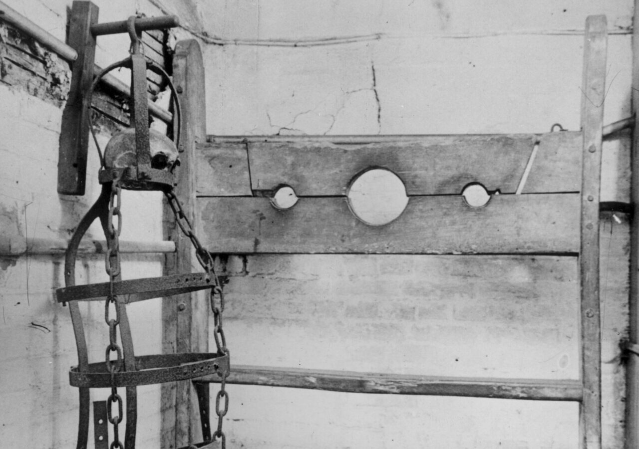 Gibbet irons and stocks on display in Winchelsea town hall in England. Within the gibbet there is a piece of skull belonging to the last man hanged in the equipment.