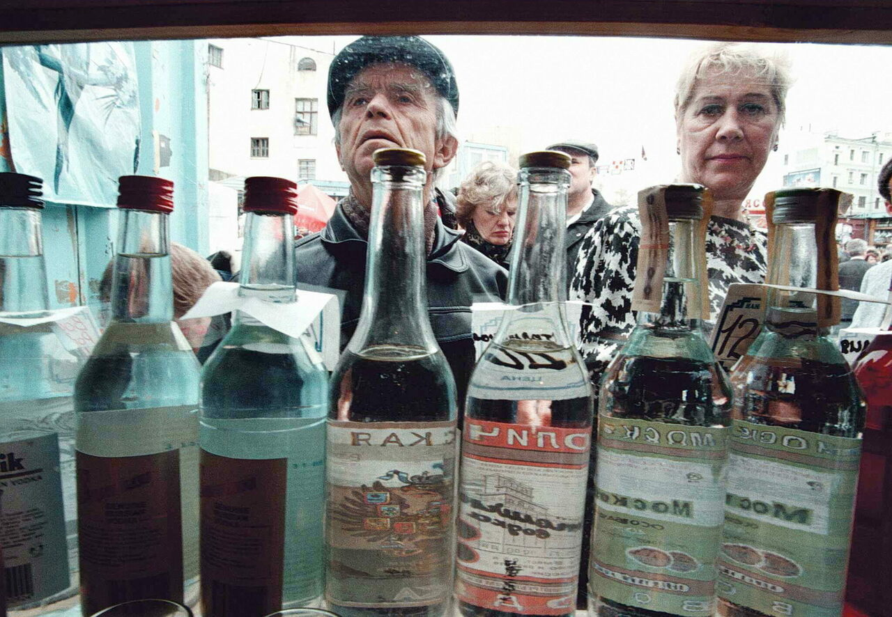 A crowd looks at different kinds of vodka for sale in a Moscow street kiosk.