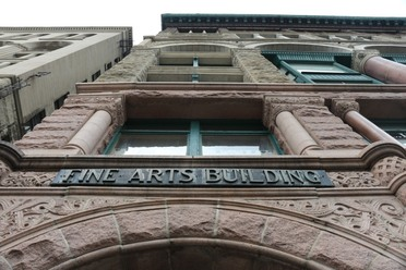 The stone above the front doorways bear the name of the Fine Arts Building.