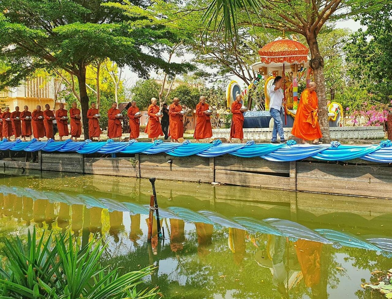 The monks collect alms in Nakhon Pathom province.