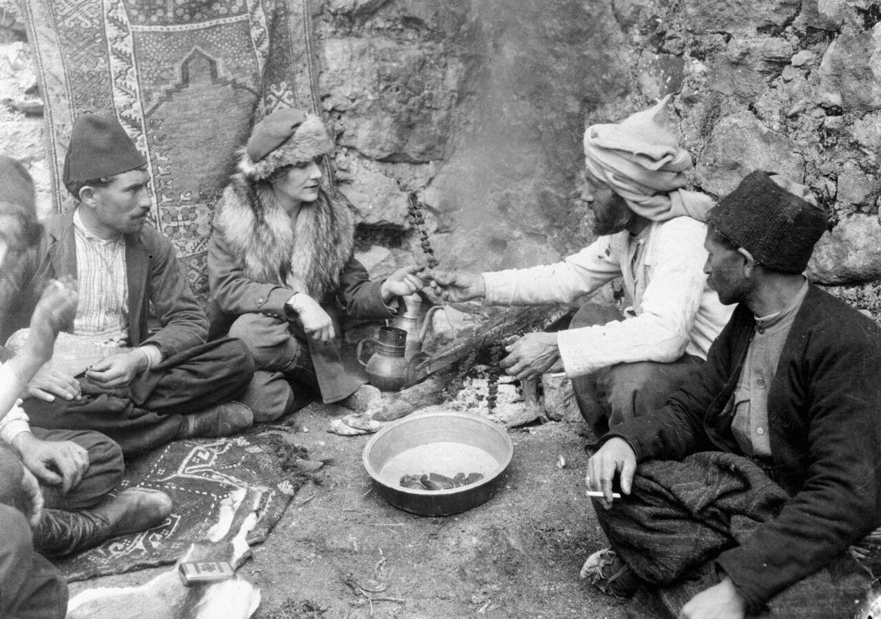 Journalist and explorer Marguerite Harrison shares a meal with a group of Bakhtiari men. (From the documentary <em>A Nation's Battle for Life</em> by Merian Cooper and Ernest Schoedsack)