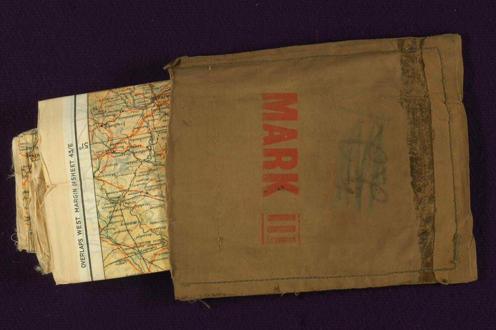 "A ""Mark III"" military escape kit, with a silk map peeking out."