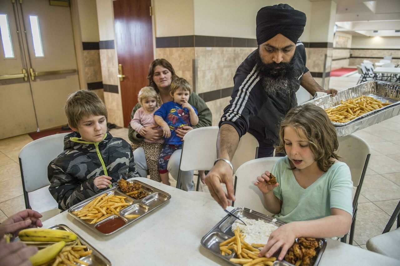 At a Sacramento gurdwara, Amarjit Singh dishes up food to a family forced to evacuate under the threat of a catastrophic dam spillway collapse in 2017.