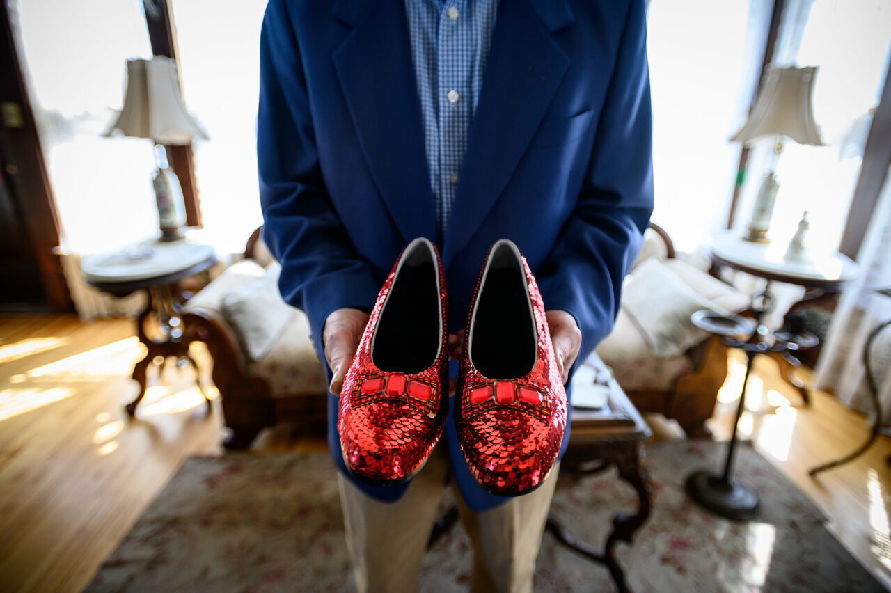 John Kelsch poses in the Judy Garland Museum with a replica of Garland's ruby slippers. The originals were stolen in 2005 and recovered in 2018.