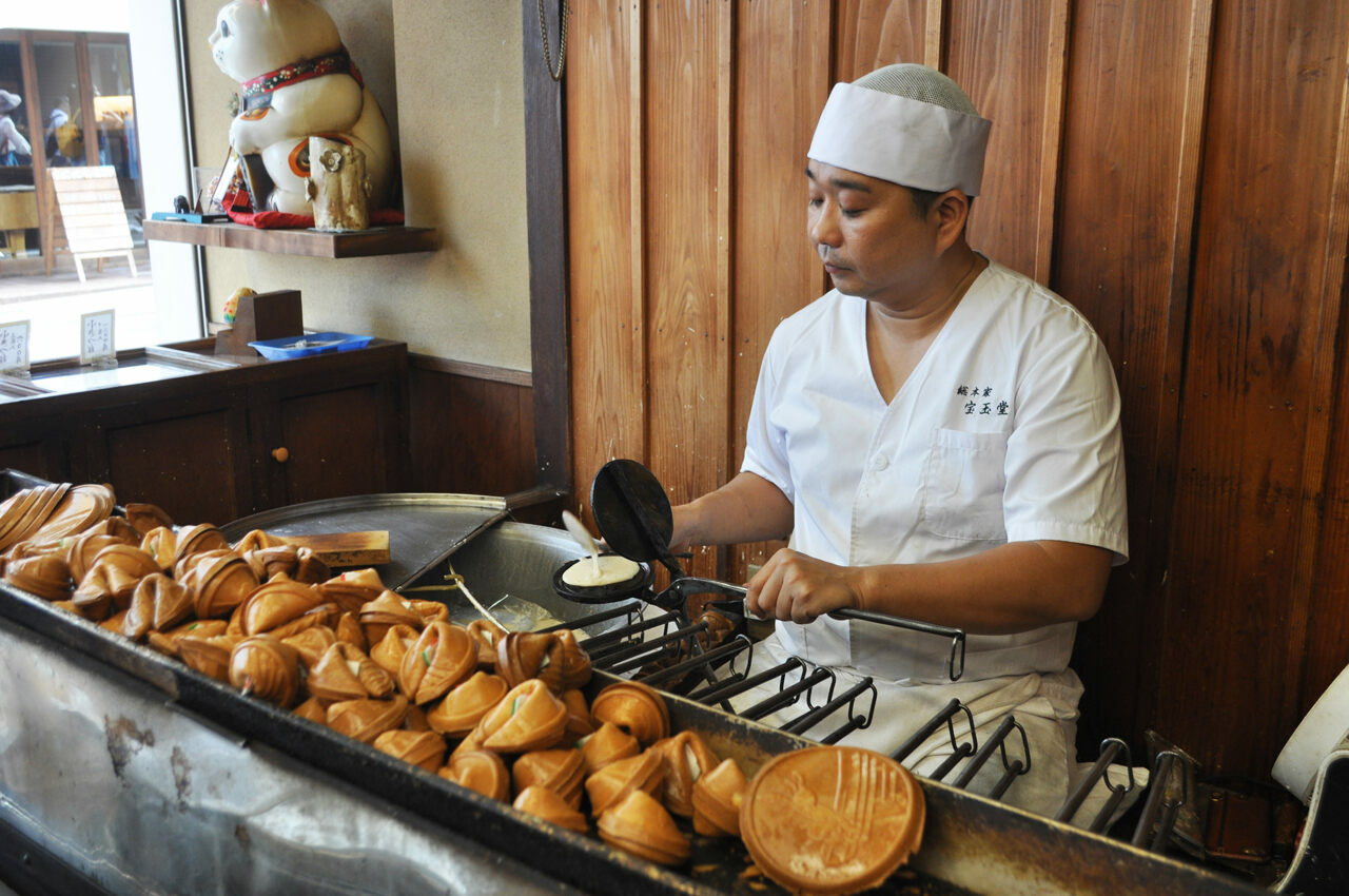 A baker makes fortune cookies at Hougyokudo in Kyoto, Japan.