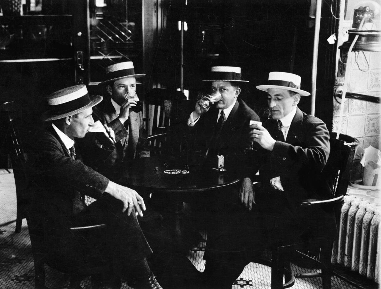 Four men in boater hats enjoy a last drink together before Prohibition begins in 1919.