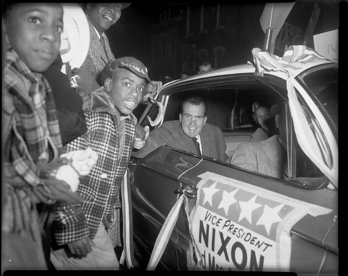 Vice President Richard Nixon and Pat Nixon greeting crowd from car, including Harold Irwin, Centre Avenue, Hill District, October 1960.