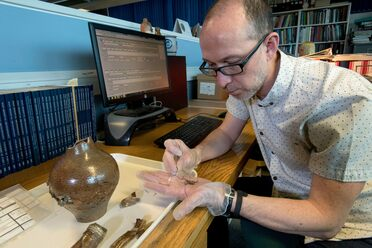 Nigel Jeffries examines bent pins found inside a witch bottle discovered at Holywell Priory.