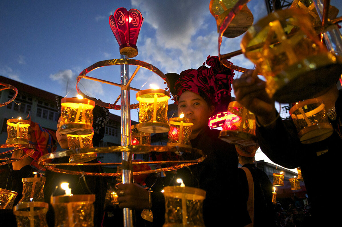Hundreds of Pa'oh people dressed in traditional clothing walk down the streets of Taunggyi holding a lantern to celebrate the Tazaungdaing Festival of Lights.