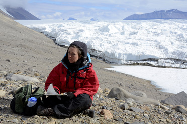 Lily Simonson in mid-sketch, next to a glacier.