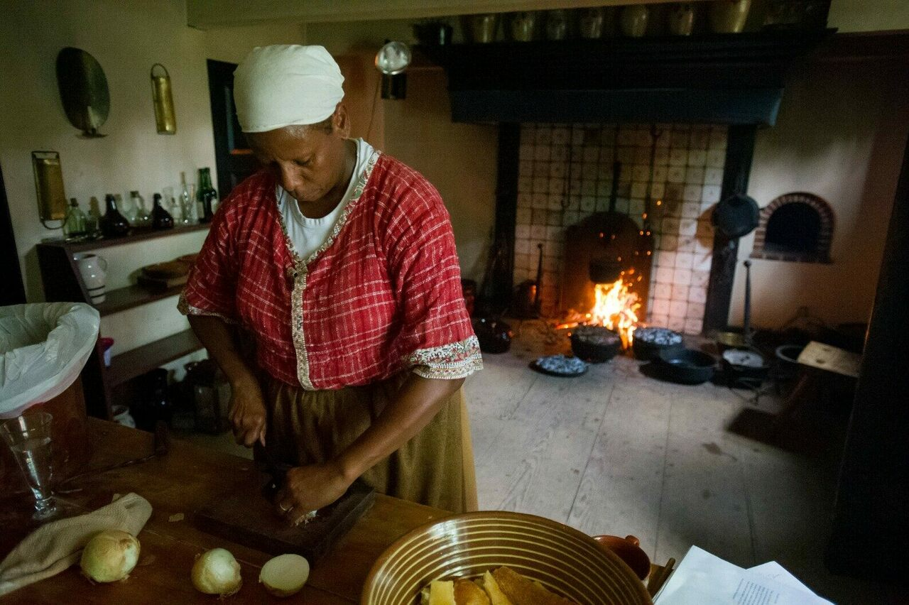 Lavada Nahon cooking a historical dinner using a jambless fireplace, a Dutch-style hearth prominent in the 17th century.