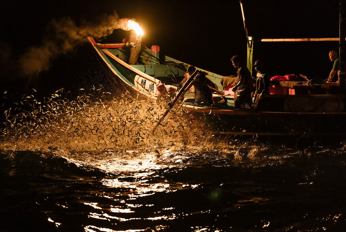 The fisherman are ready with their nets as the sardines leap towards the fire.