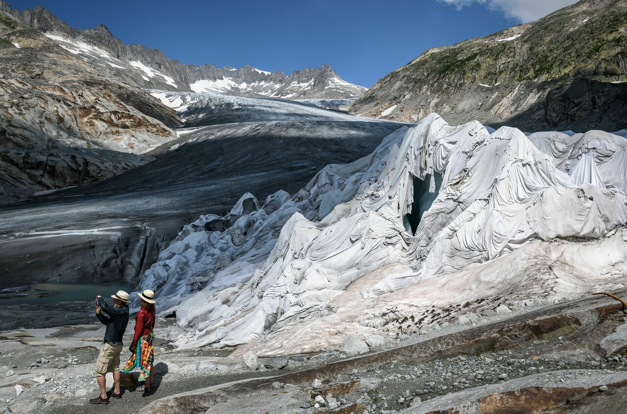 Visitors stand next to the Rhône glacier in August 2018.