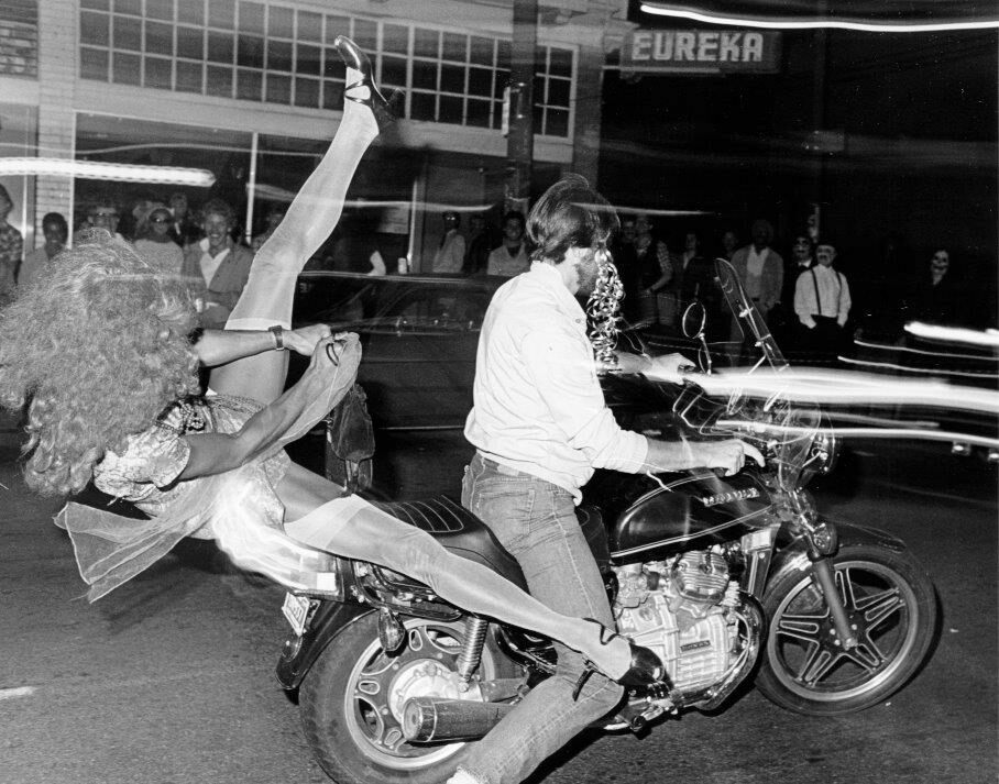 Two partiers drive past the Eureka Bar, off Castro Street, on Halloween 1982.