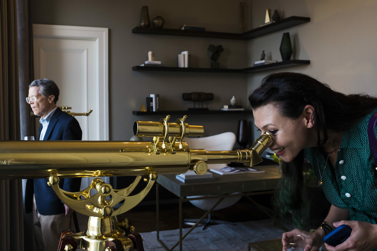 A guest takes a mapmaker's point of view, peeking through a telescope.