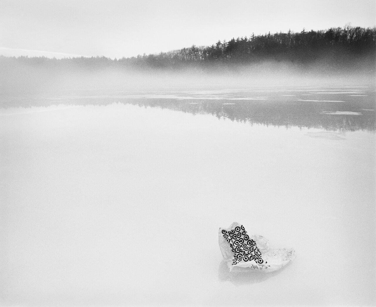 "A Target bag rests on the surface of Walden Pond. Part of S.B. Walker's 2017 photo series, ""Walden."""