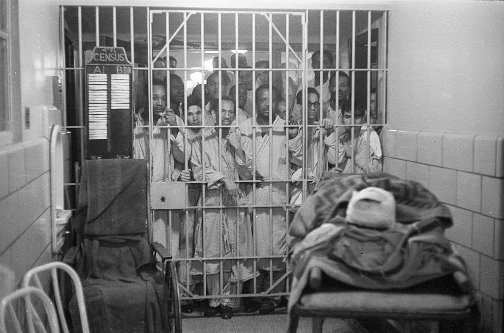 Prisoners at Rikers Island watch through bars as an injured airline passenger waits for transport to a New York hospital.