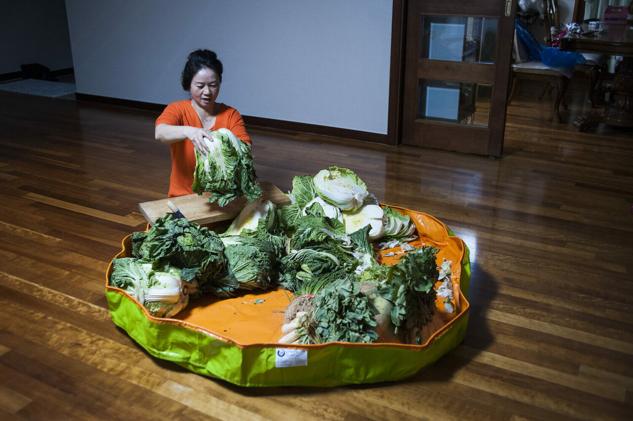 Photographer Sangsuk Sylvia Kang's mother Kyung Ae Lee performs <em>kimjang</em>, the practice of making kimchi, at her home in South Korea.