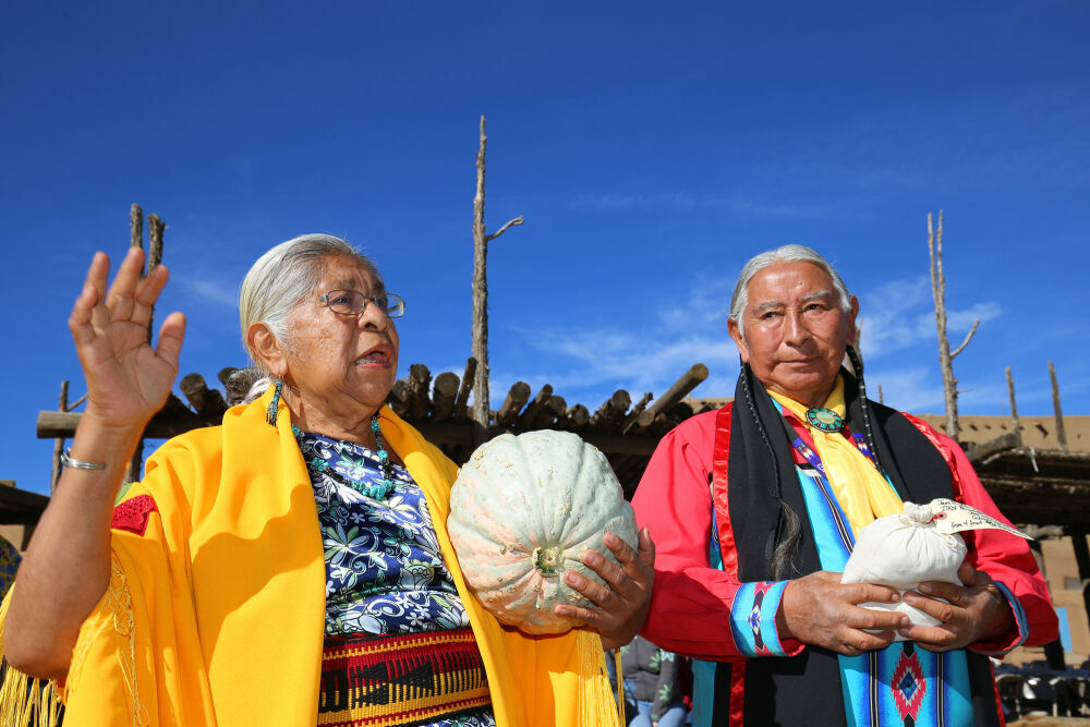 Henrietta Gomez and Gilbert Suazo, Sr., receive a Taos Pueblo squash in 2018.